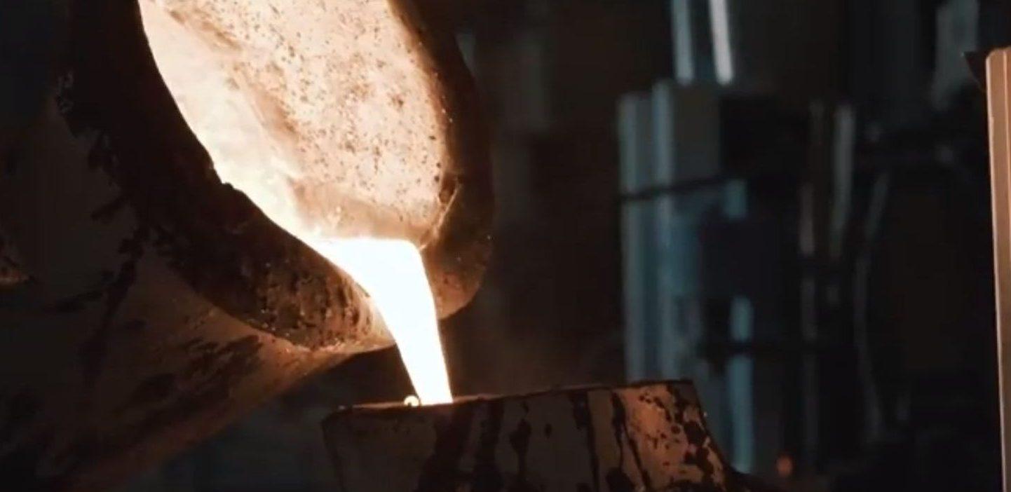 Ein Kübel mit extremer heißer Flüssigkeit wird in ein anderes, kleineres Gefäß geleert.