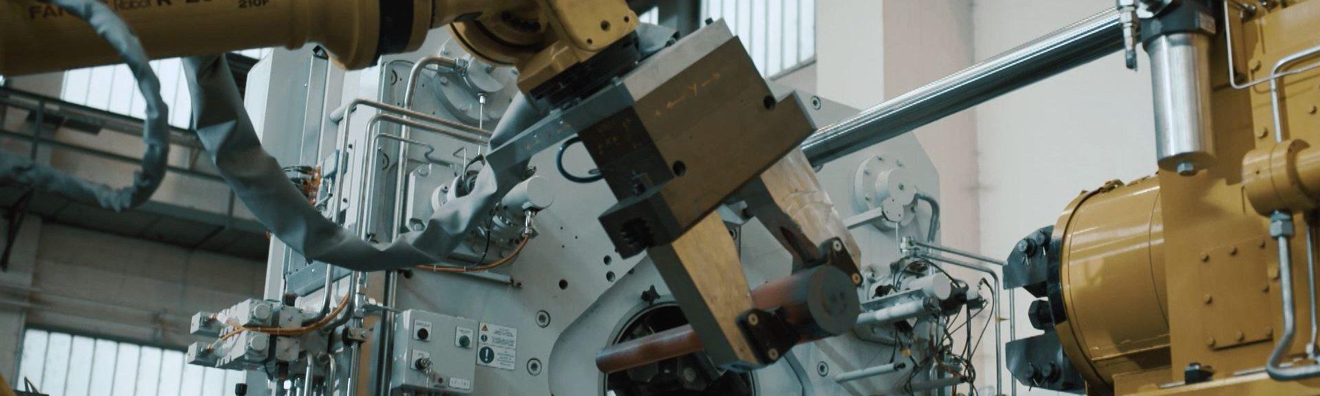 Ein gelber Roboterarm bei der automatischen Bestückung einer Rotationsschmiedeanalge mit einem Werkstück.